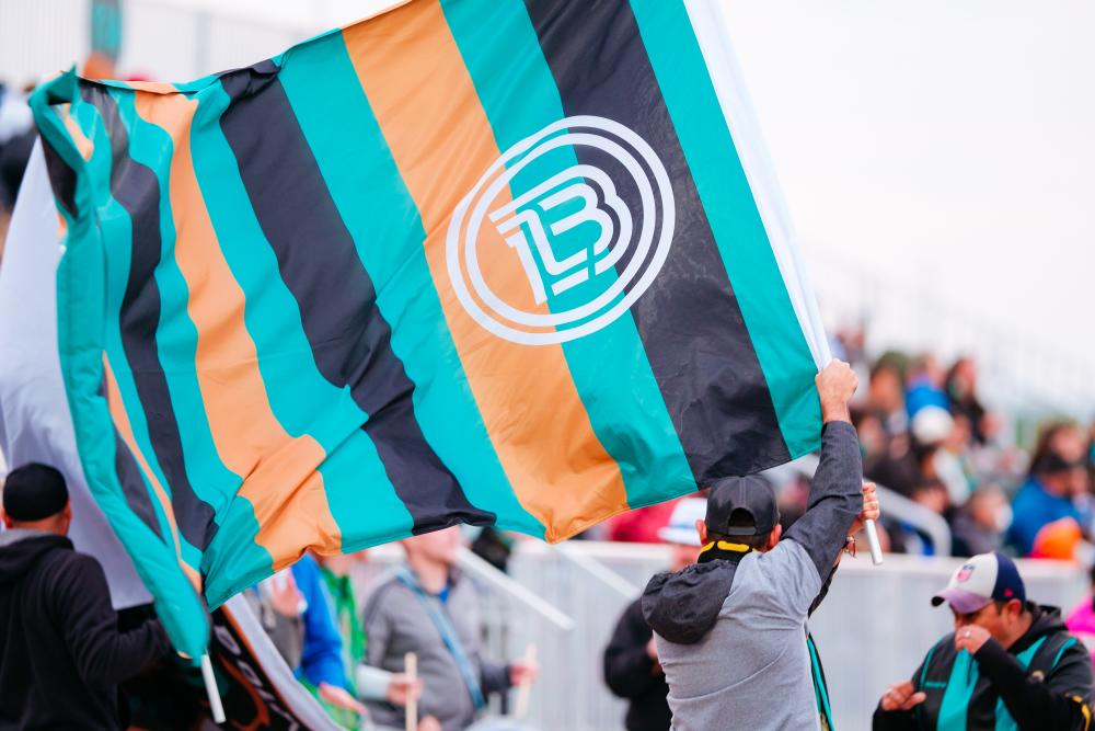 Man waving Austin Bold FC Flag at Bold Stadium in Austin Texas