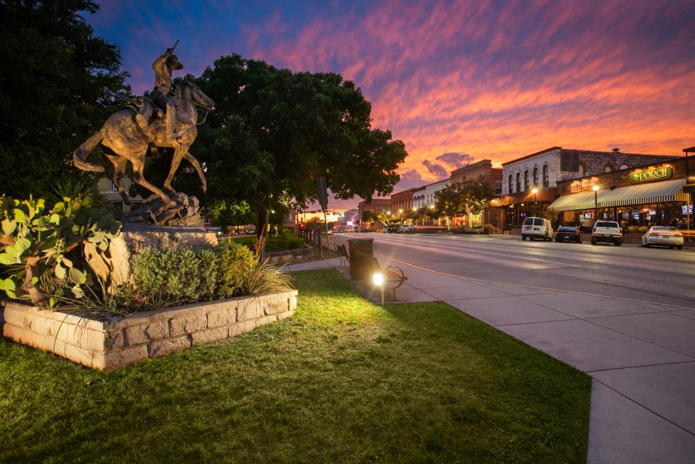 Statue and shops in Downtown San Marcos Texas at Sunset