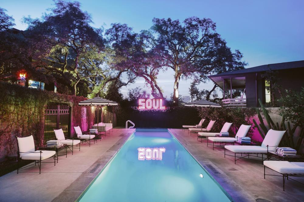 Hotel Saint Cecilia Pool at Dusk with sign reading soul in austin texas