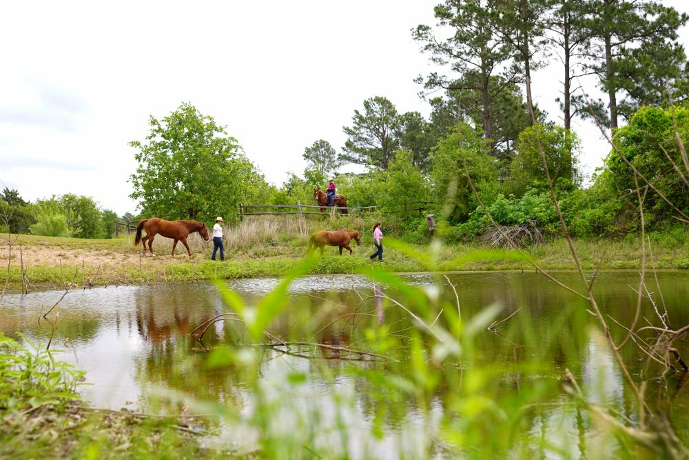 people horseback riding at McKinney Roughs Nature Park near Bastrop Texas
