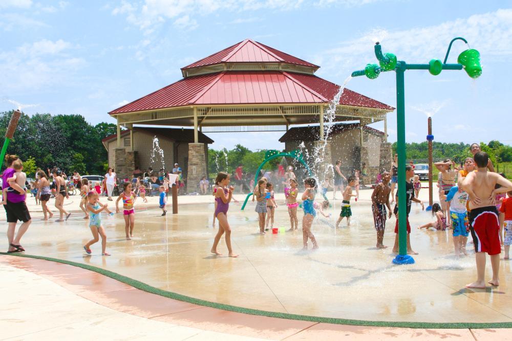 Kids cooling off in a splash pad at Buckner Parl