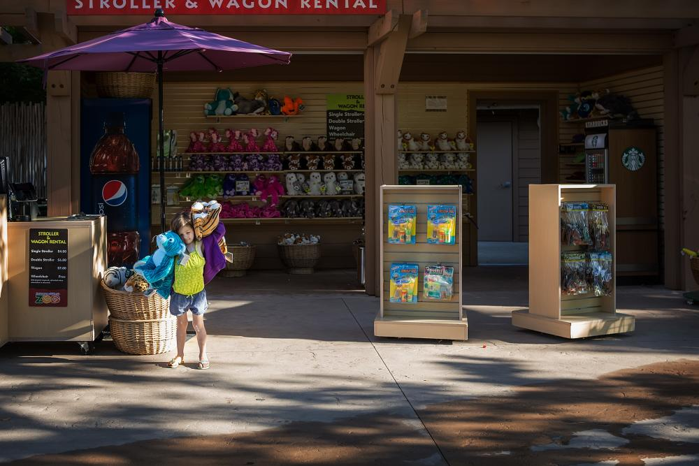 A little girl purchasing souvenirs at a Gift Kiosk in the Fort Wayne Children's Zoo in Indiana