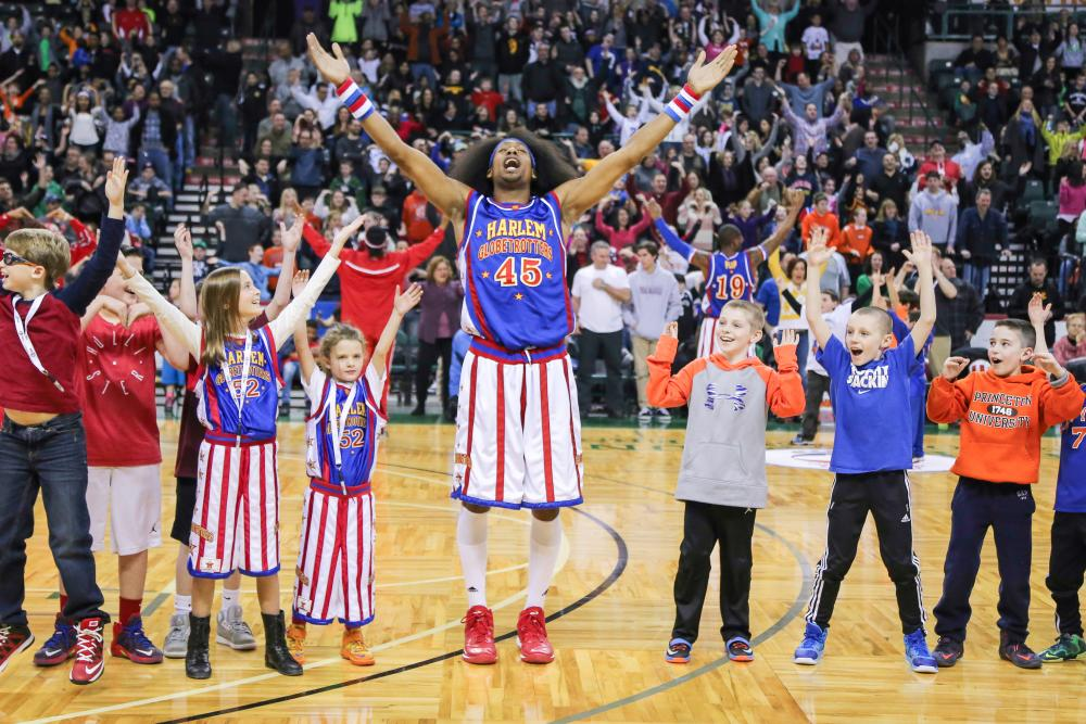 A Harlem Globetrotter raising arms with a bunch of kids on the basketball court