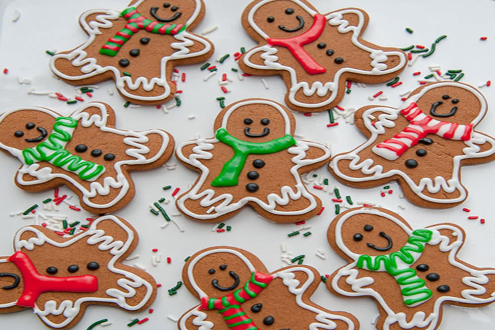 Decorated Gingerbread people with frosting scarves, buttons, and smiley faces on a table with sprinkles