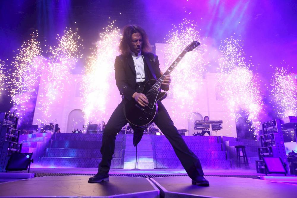 A guitarist shreds on the INTRUST Bank Arena stage with flames shooting up behind him