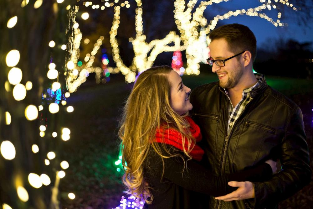 Couple holding on to one another under Christmas lights at Illuminations at Botanica Wichita KS