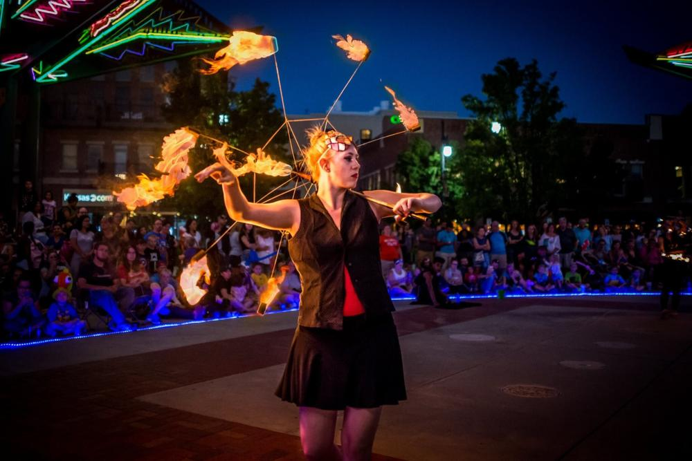 An artist performs her routine with fire in front of a large audience for First Friday in Wichita