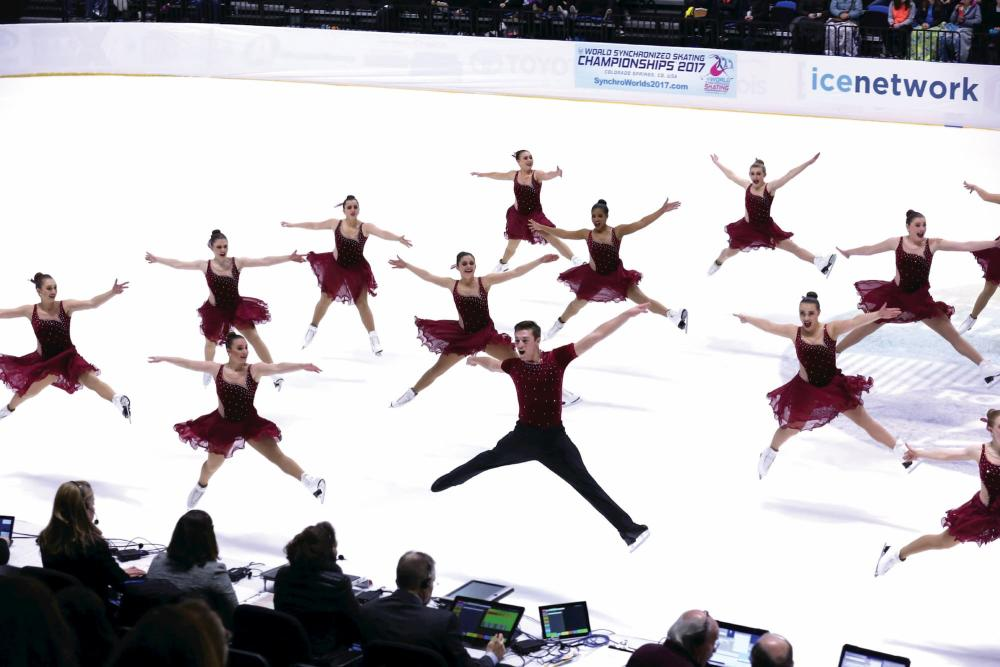 Synchronized skaters all jump in unison on the ice rink