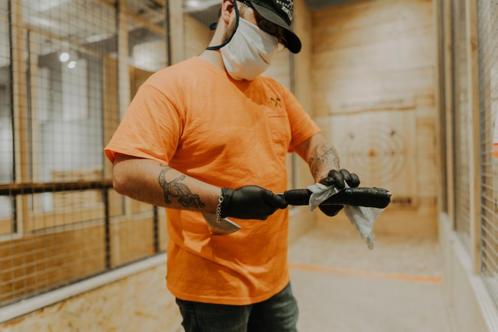 Blade and Timber Coach Wearing Mask and Sanitizing Axes