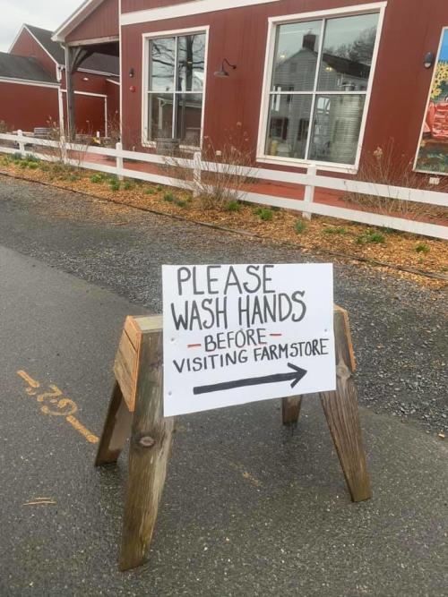 An image fromTerhune Orchards with a sign that requests visitors to wash hands before entering the premises