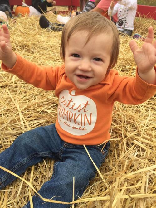 A cute little boy wearing a pumpkin shirt in a hay pile