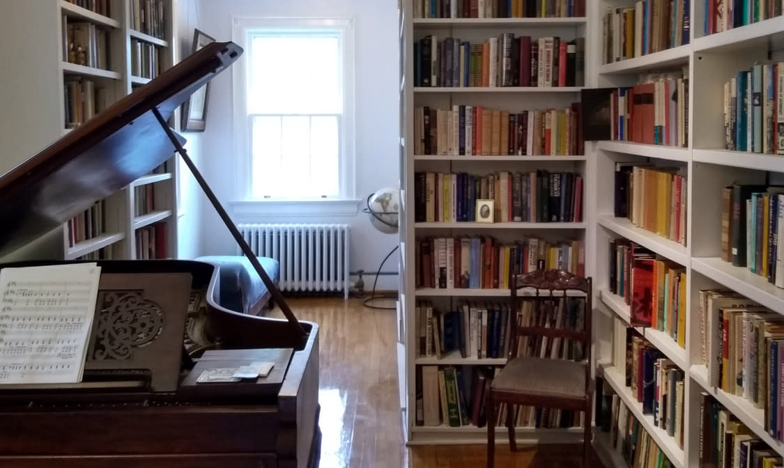 Piano and Bookshelves at Between the Covers Literary Bed and Breakfast
