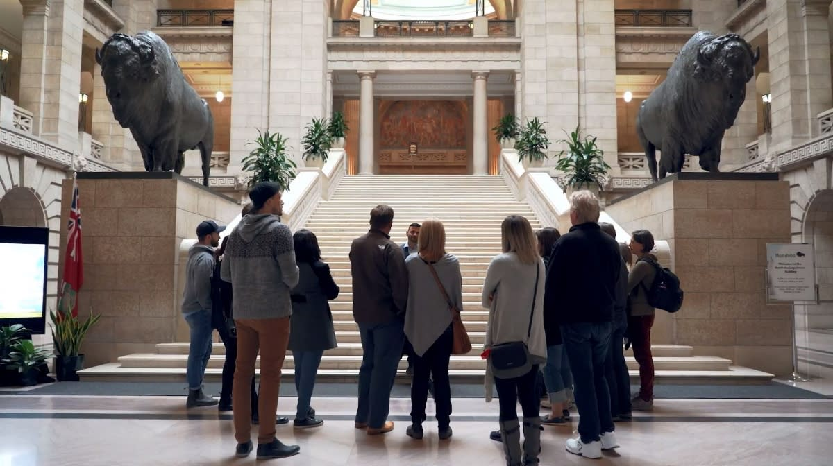 Dr. Frank Albo speaks to a group of people at the foot of the stairs in the Manitoba Legislative Building