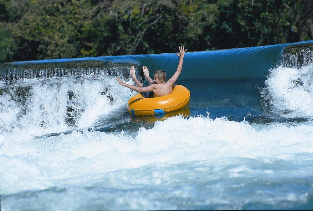 child waves arms in innertube on waterfall in San Marcos Texas