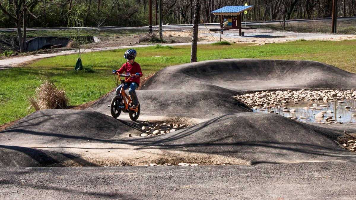 Boy on a bicycle with a helmet on the Mini bicycle pump track and kids loop trail