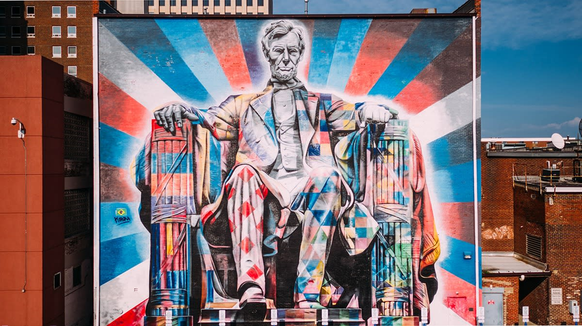 A large mural of Abe Lincoln sitting painted in brightly colored patterns primarily with red, blue, and white.