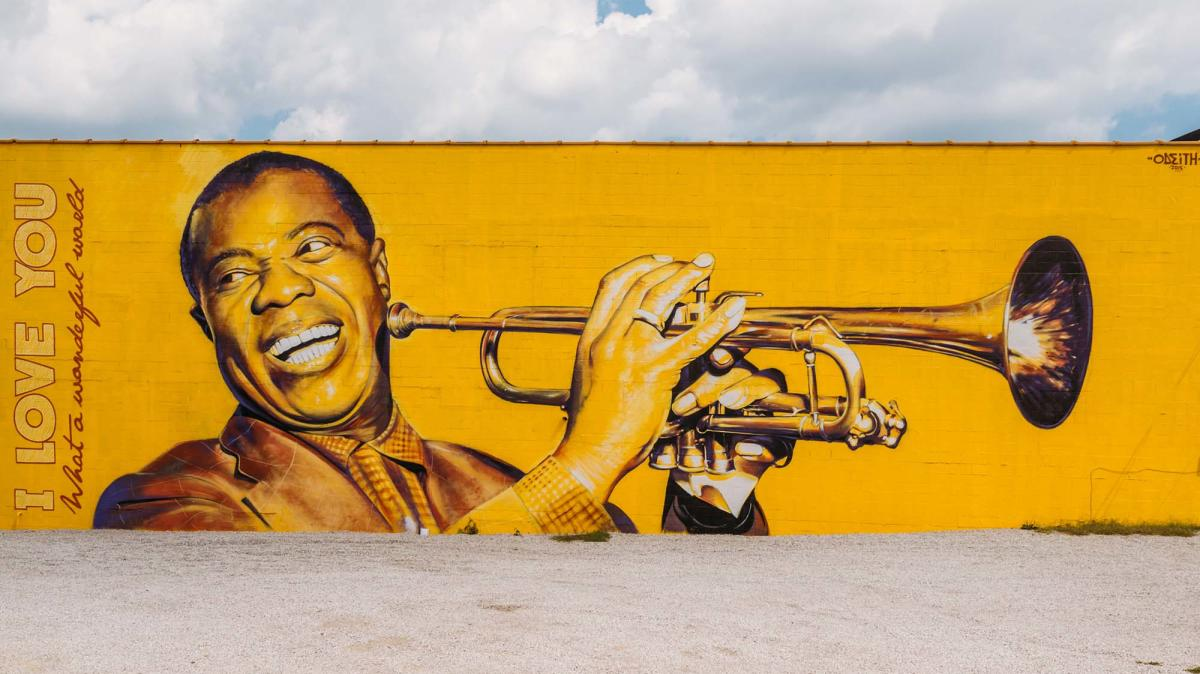 "Photorealistic, bright yellow mural of Louis Armstrong smiling and holding his trumpet up to play. The words ""I love you"" and ""What a wonderful world"" are painted on the left hand side of the mural."