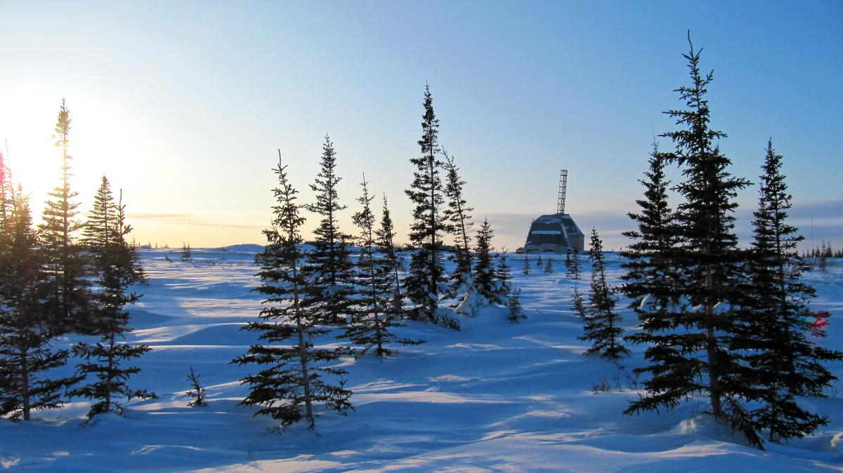 Looking across the snow covered tundra, through the trees at the historic Rocket Range in Churchill
