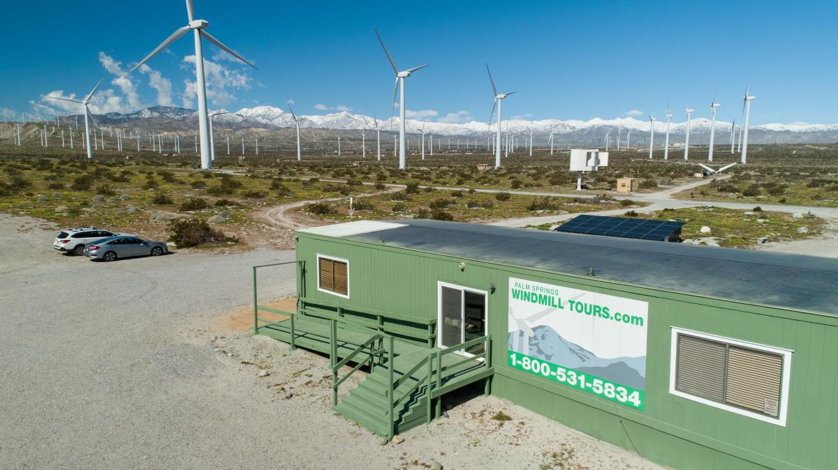 The office of Palm Springs Windmill Tours sits amid a windmill farm with wind turbines in the background.