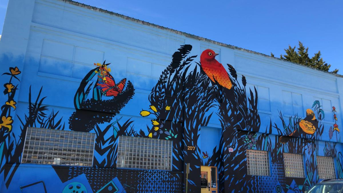 A colorful mural beckons guest to the Refinery Creator Space in Asheville, NC