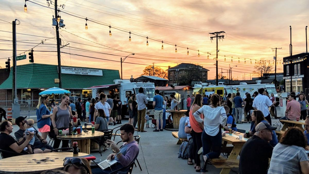 People standing and sitting at tables at a Food Truck Park