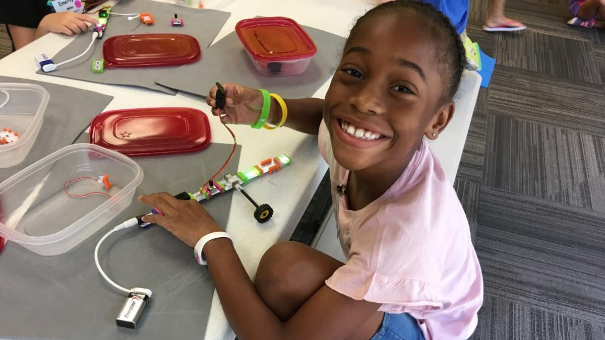 Little girl smiling while building a battery powered device at The Muse