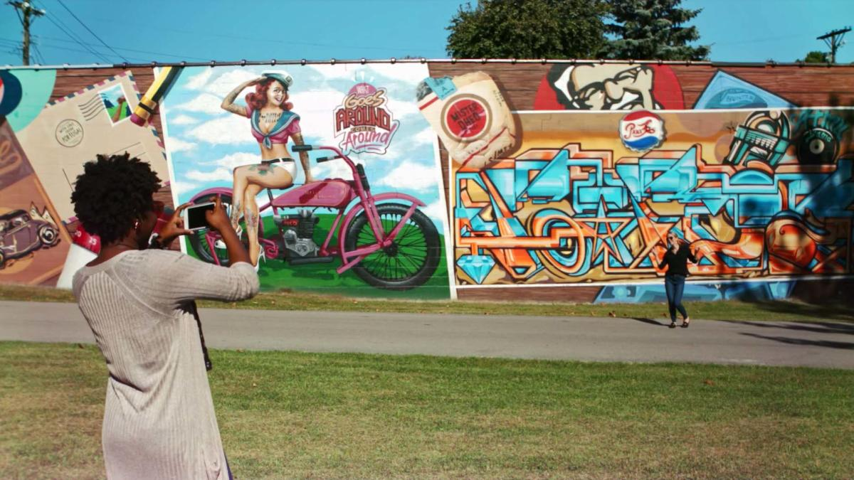 A woman photographs her friend posing for a photo in front of a series of huge, vibrant murals.