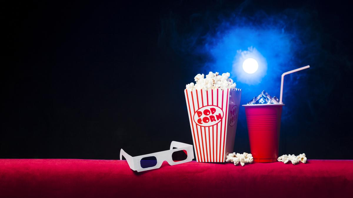 A box of popcorn, a red cup with ice in it and a pair of 3D glasses sit on a red surface in a movie theatre.