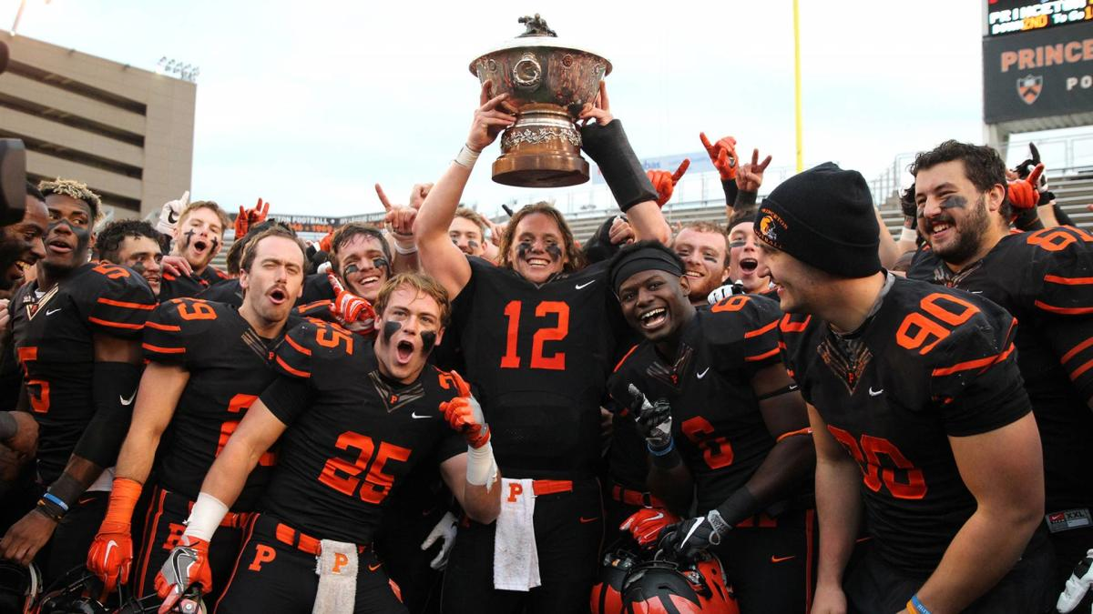 The Princeton Tigers football team holding up a large bowl trophy