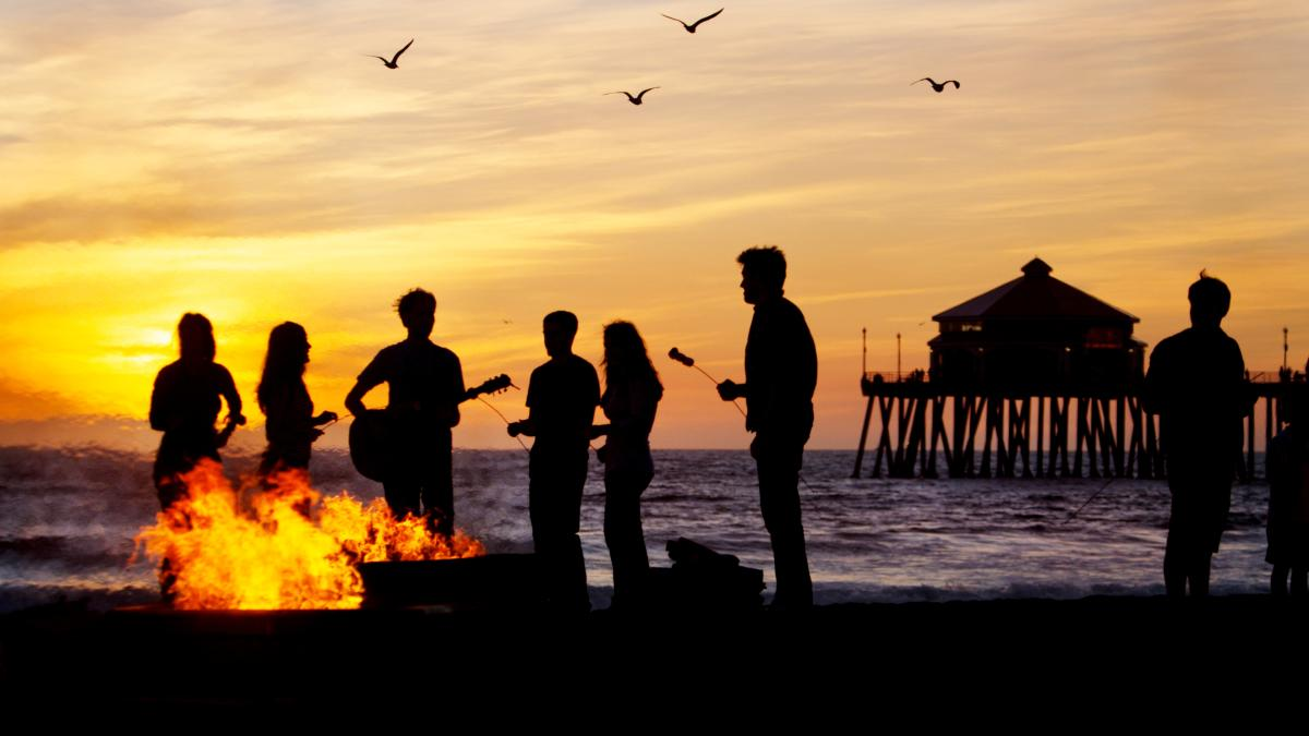 Friends on the beach at sunset playing music and roasting marshmallows by a bonfire in Huntington Beach