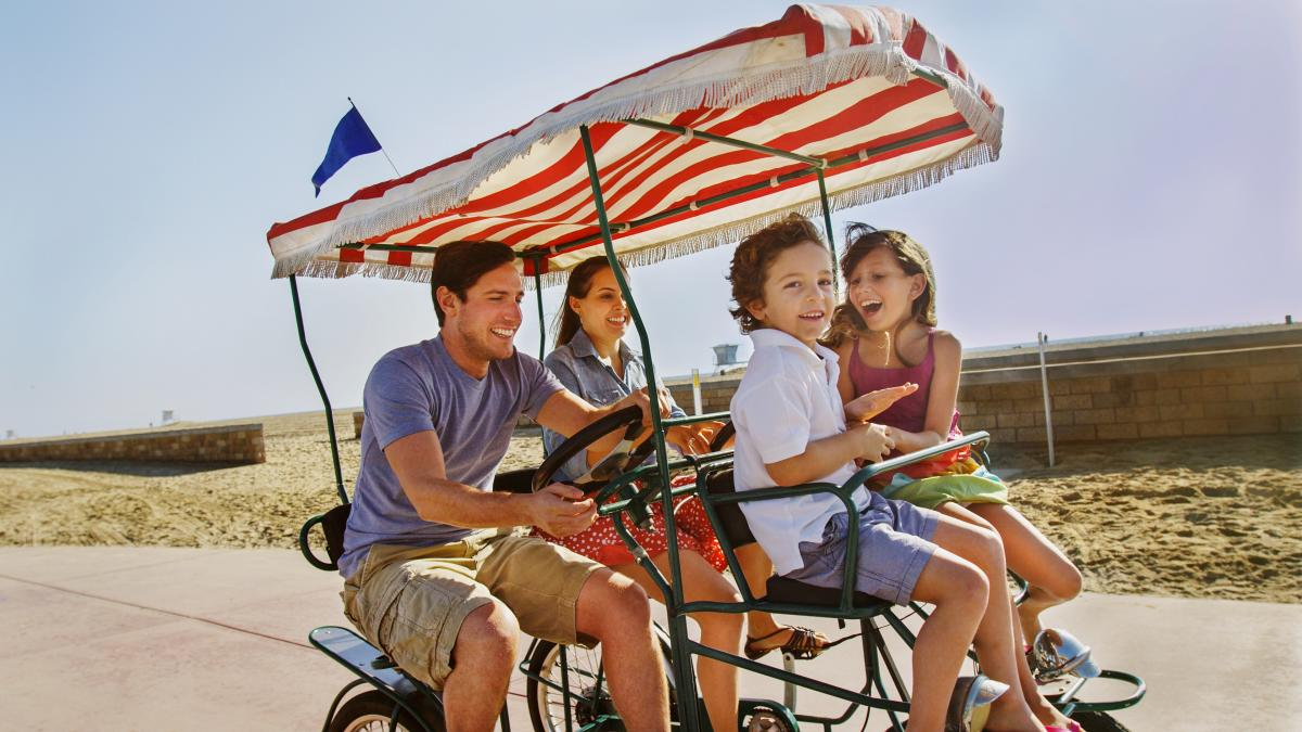 A family of four in a 4 seater bike riding a bike trail in Huntington Beach