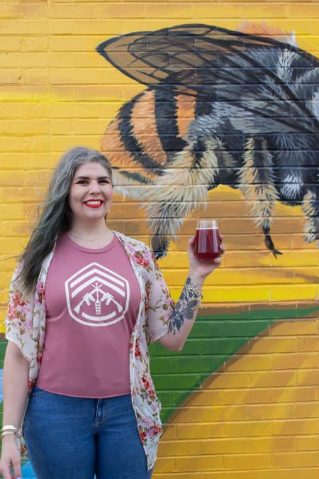 Woman standing in front of bee mural holding a glass of beer
