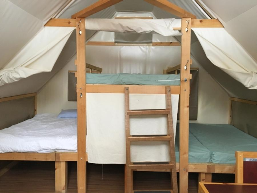 Three bunk beds in triangular shape inside oTENTik