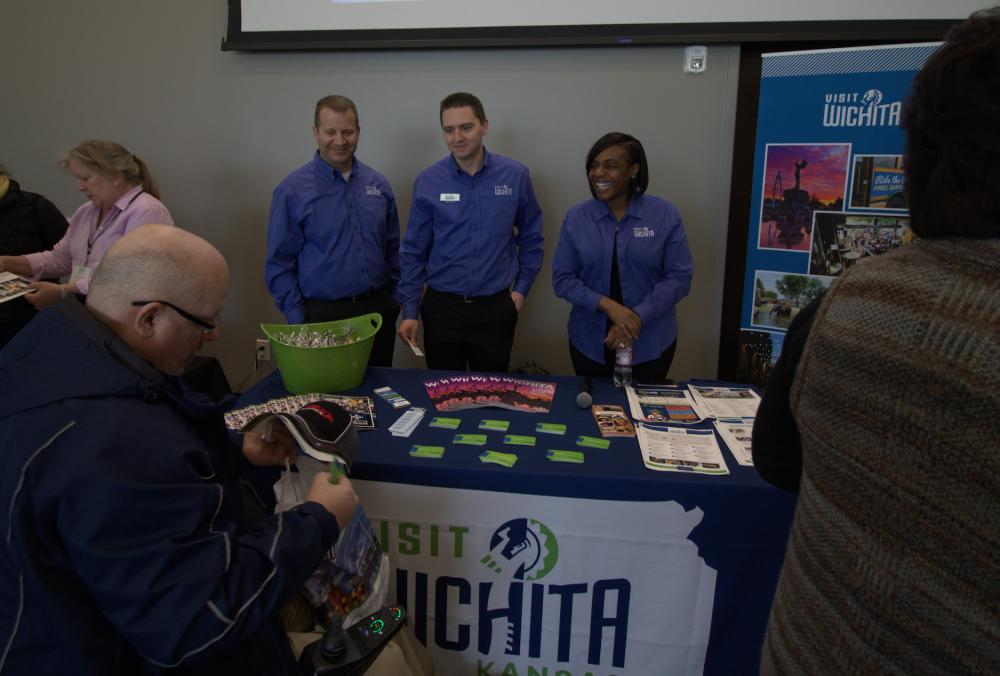 Three members of the Visit Wichita Sales Team visiting with people at their booth for a conference