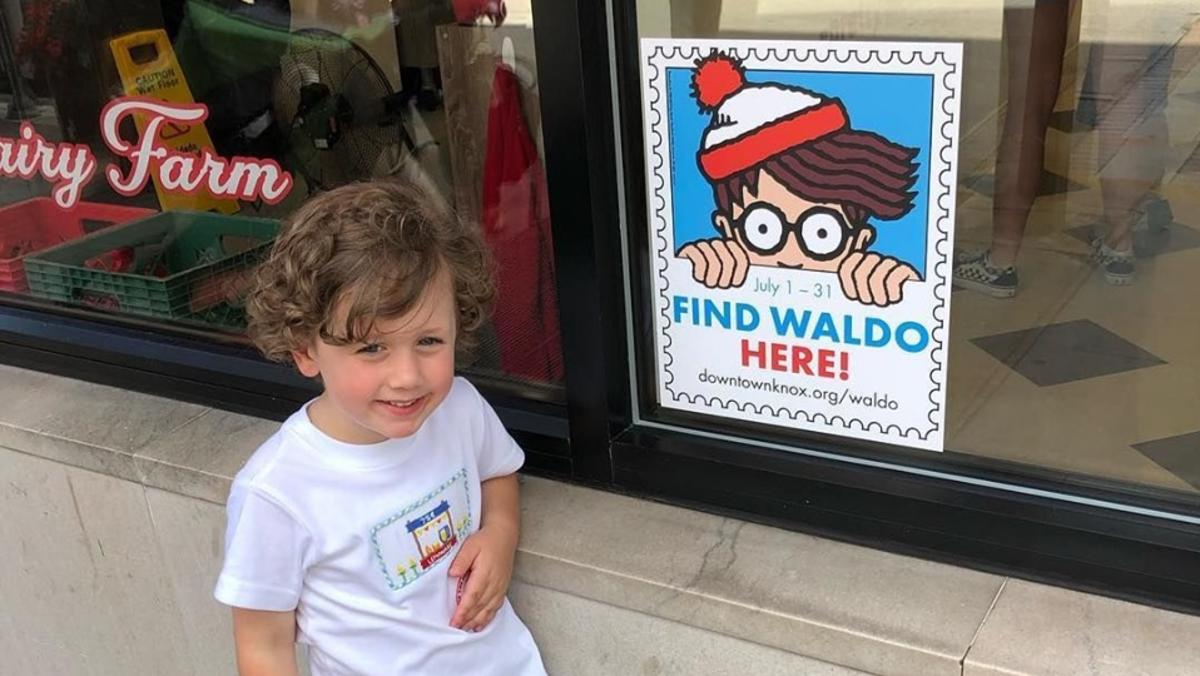 Kid smiling next to a Where's Waldo poster in downtown Knoxville