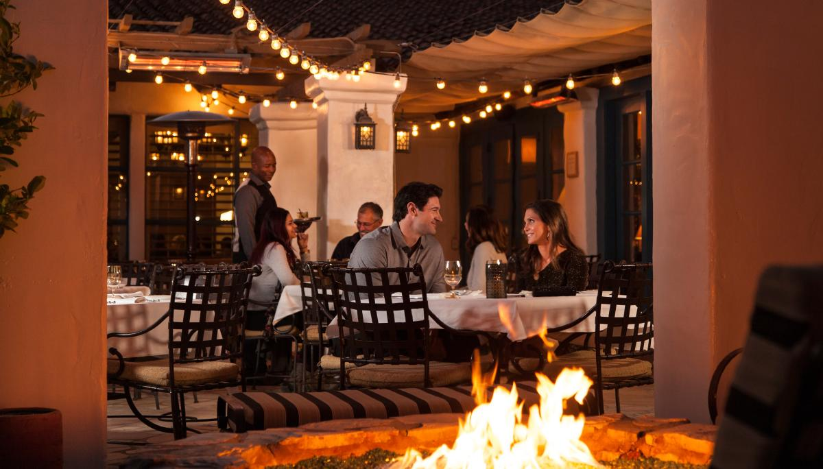 Couple dining at La Quinta Resort next to a fire pit.