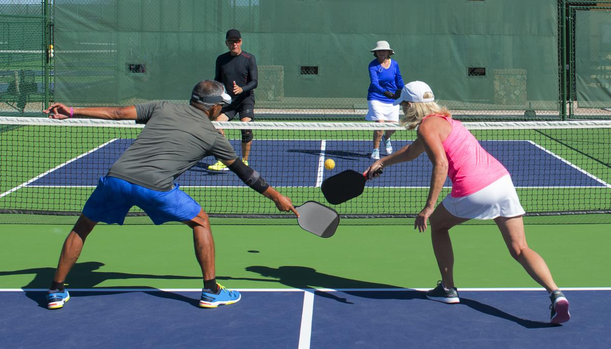 2 couples playing pickle ball on an outdoor court