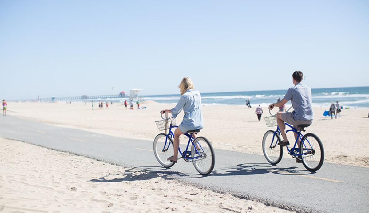 A man and woman biking on a trail near the beach in Huntington Beach