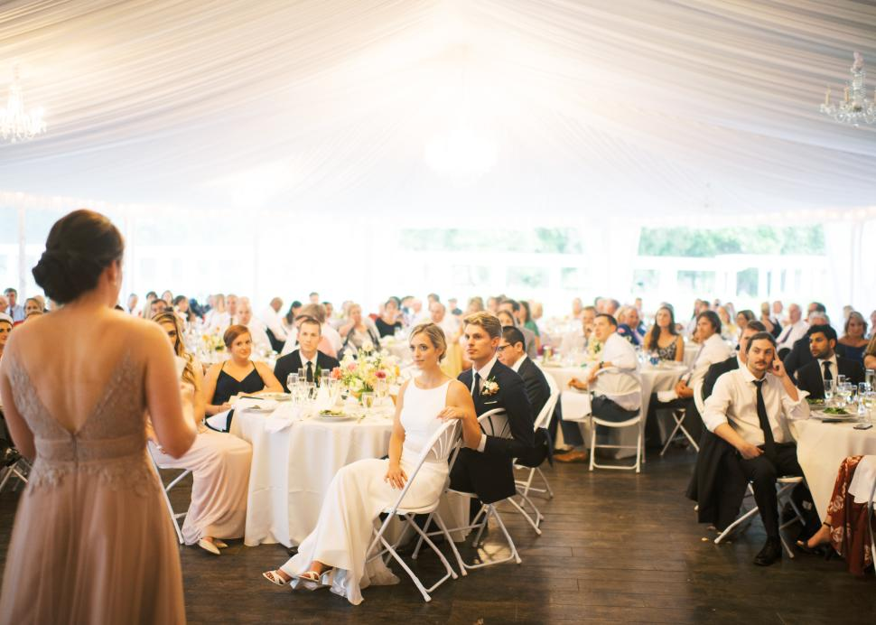 Maid of Honor giving toast inside tent