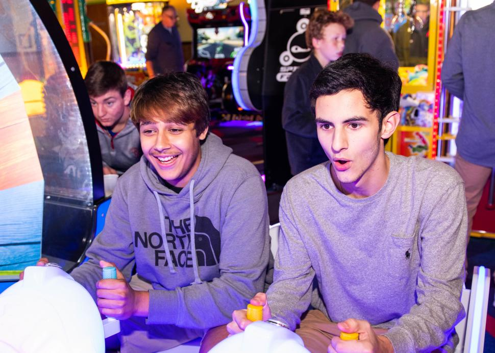 Two boys play an arcade game inside of the Roseland Family Fun Center