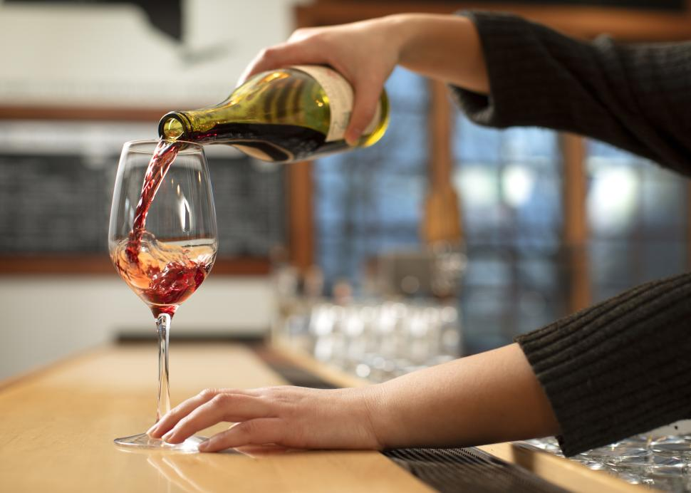 Wine being poured into a glass at New York Kitchen; Photo Credit: Grant Taylor Photography