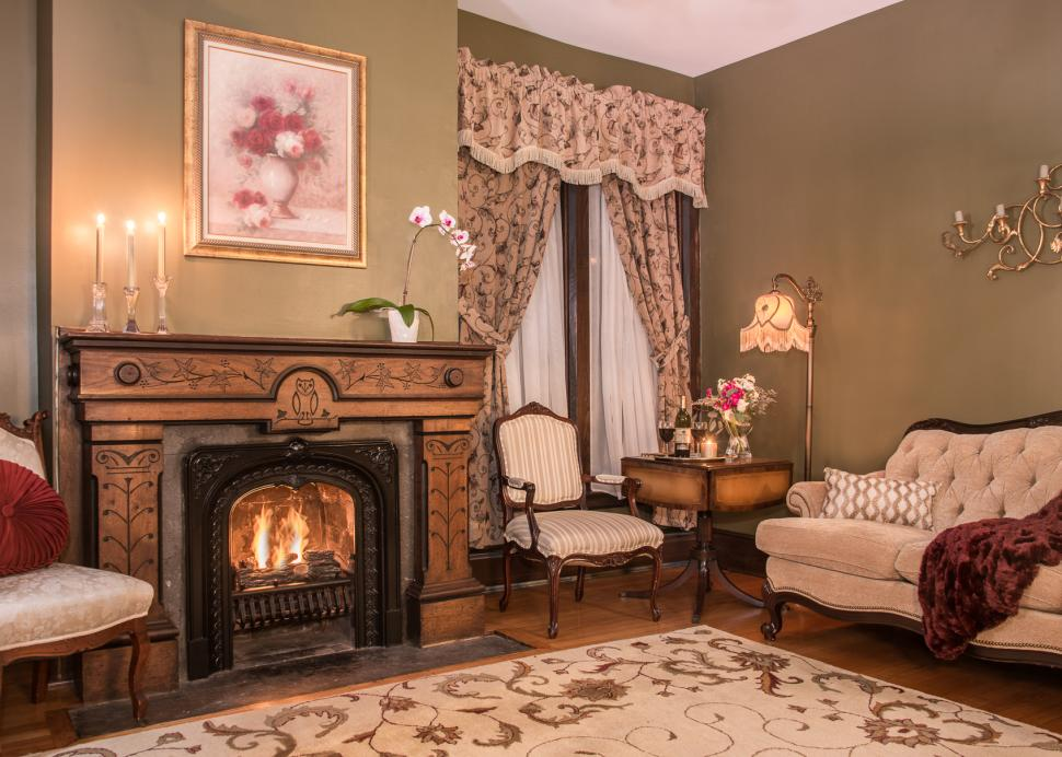 Interior of the Penfield Suites parlor room with the fireplace running