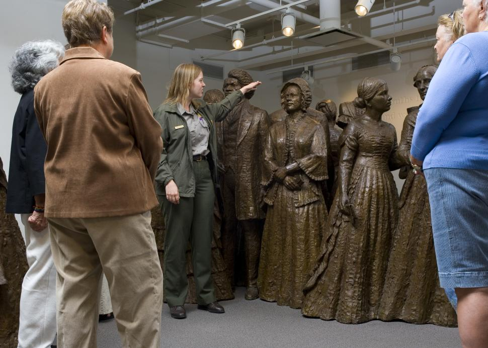 Guide, tour group, and statues of women at Women's Rights National Historical Park
