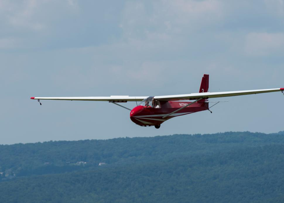 Plane soaring in front of mountains at National Soaring Museum