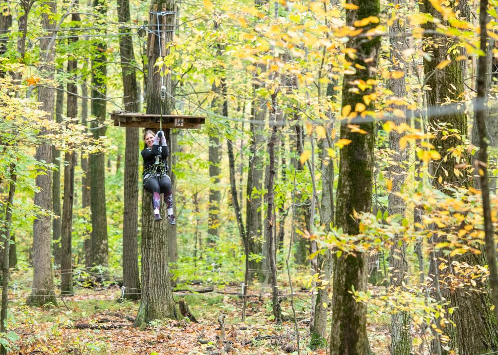 Photo of a customer zip lining to the ground at Bristol Mountain Ariel Adventures