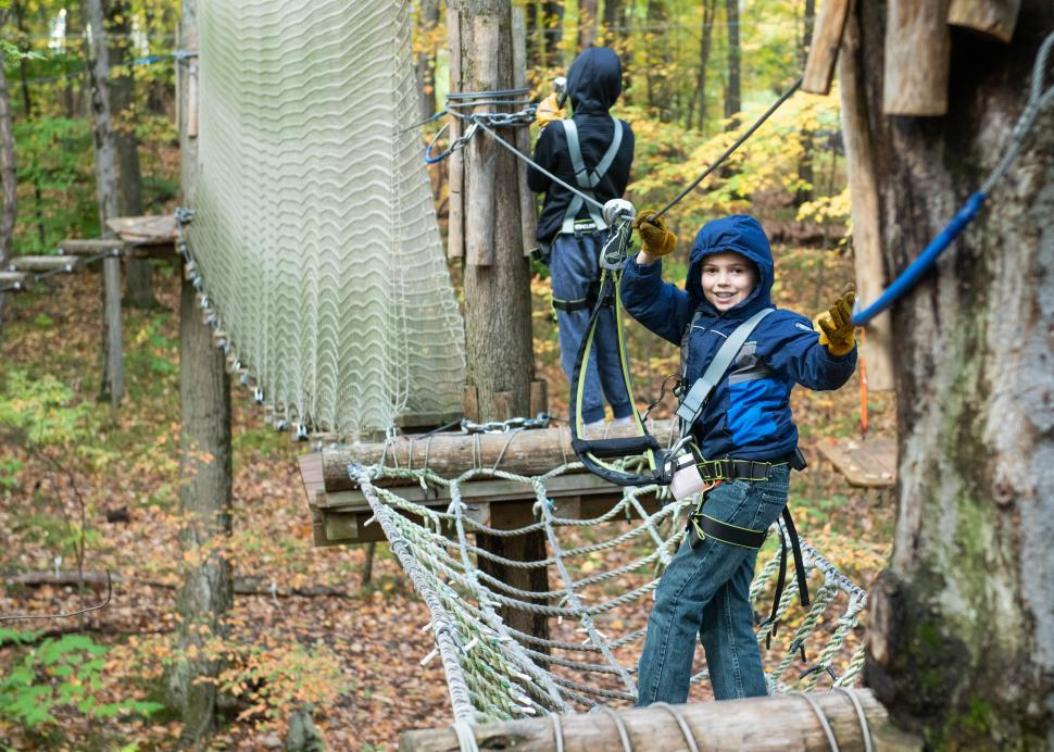 A customer posing on the obstacle course in the trees at Bristol Mountain Arial Adventures