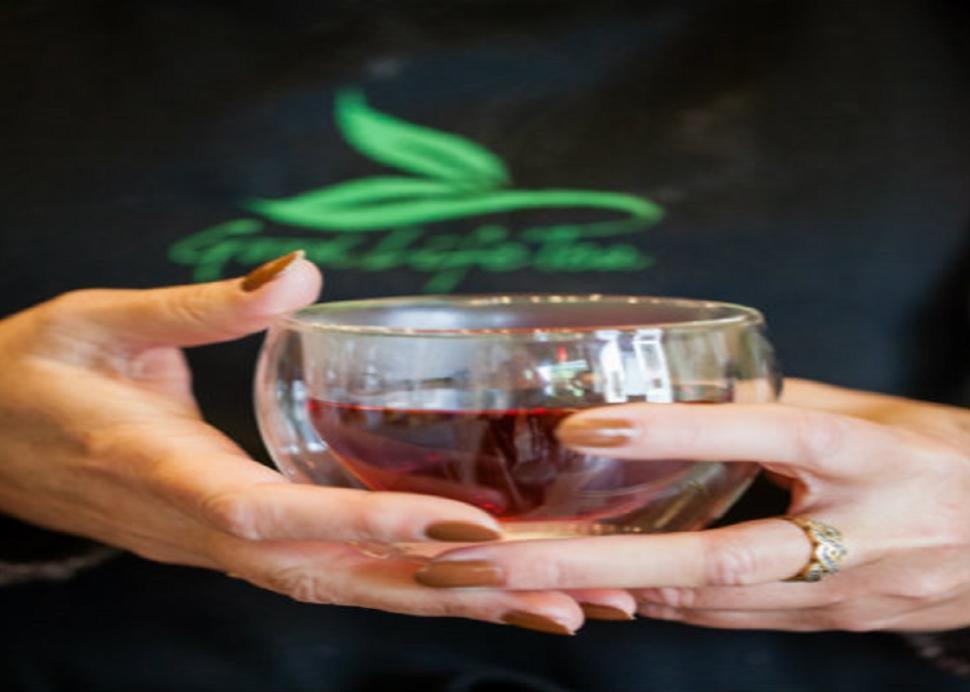 Closeup on hands holding a glass of tea at Good Life Tea