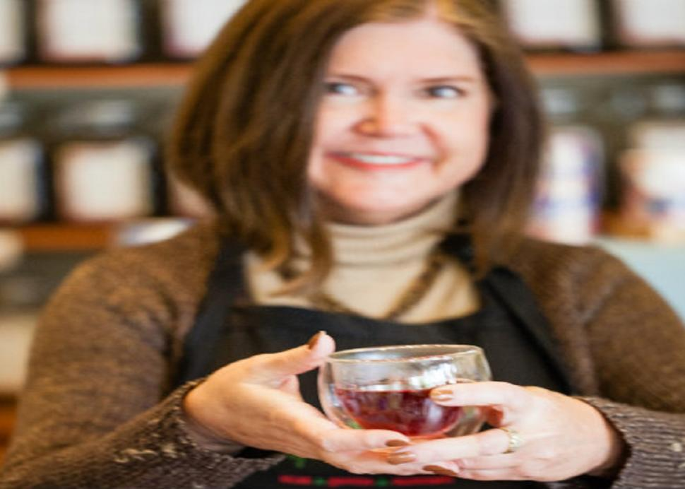 A woman holds up a glass of tea inside of Good Life Tea