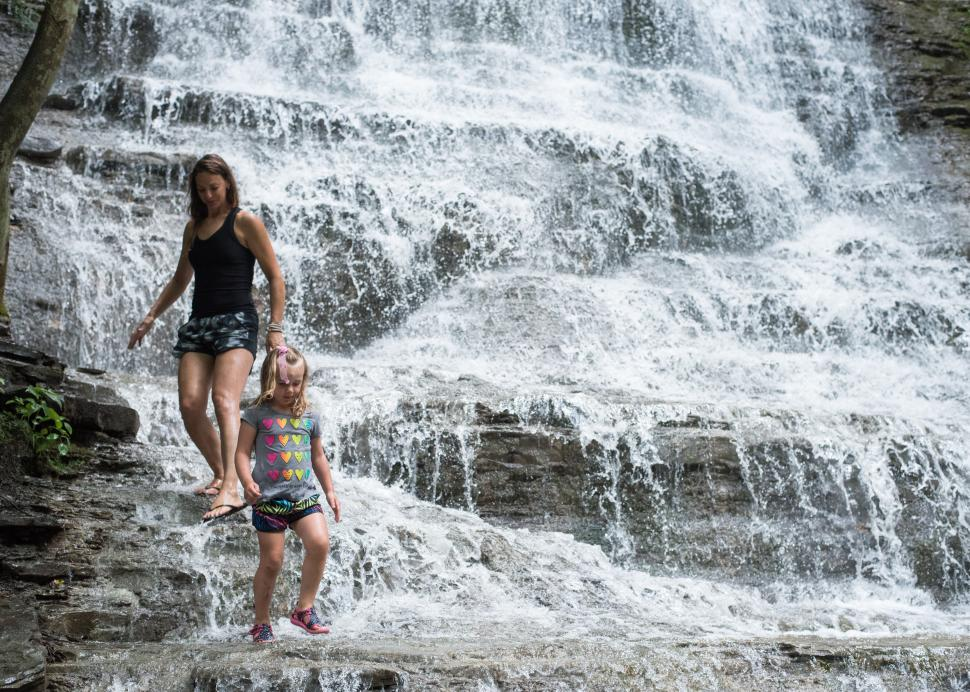 Hikers climb down a waterfall at Grimes Glen