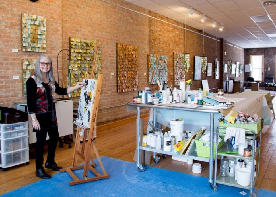 Jeanne Beck poses for a photo while painting in her studio in Canandaigua